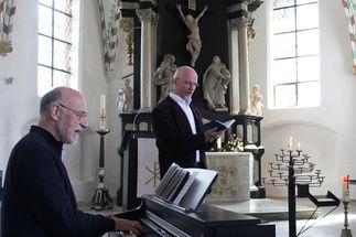 Ein Mann im Profil, sitzend am Klavier. Ein Mann dahinter stehend mit Mappe in der Hand. - Copyright: Oliver Pries