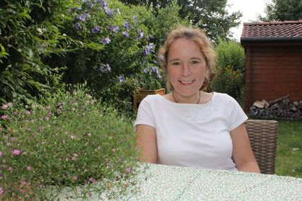 Frau sitzt am Tisch in einem Garten. - Copyright: Oliver Pries