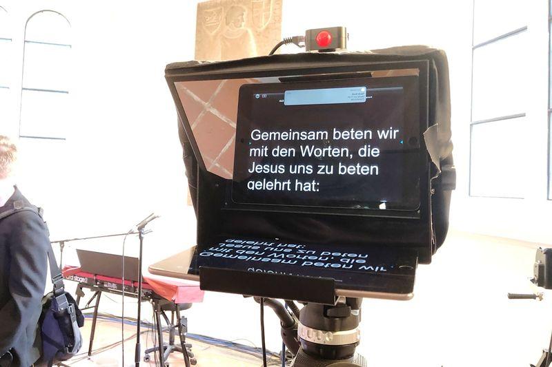 """Ein Teleprompter mit dem Text """"Gemeinsam beten wir mit den Worten, die Jesus uns zu beten gelehrt hat""""."""