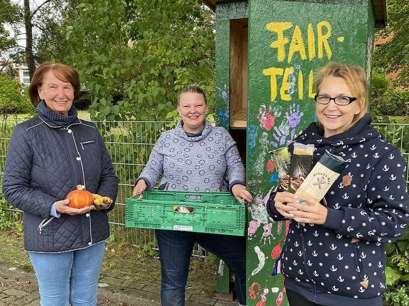 Drei Frauen stehen mit Obst und Konserven vor einem grünen Schrank und lächeln in die Kamera.