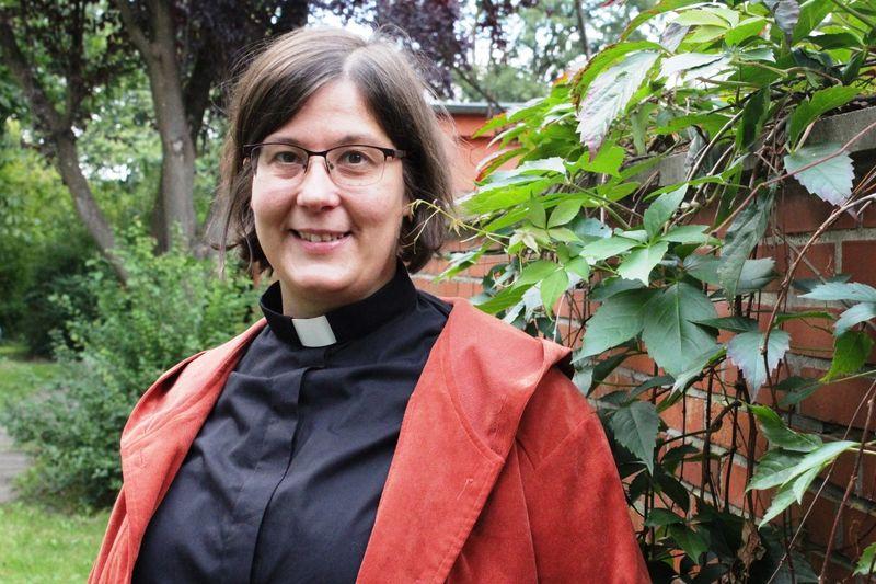 Eine Frau mit Brille, im Hintergrund eine Backsteinmauer mit Weinranken.