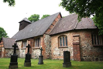 Drei Steinkreuze stehen vor der St.-Laurentius-Kirche auf grünem Rasen
