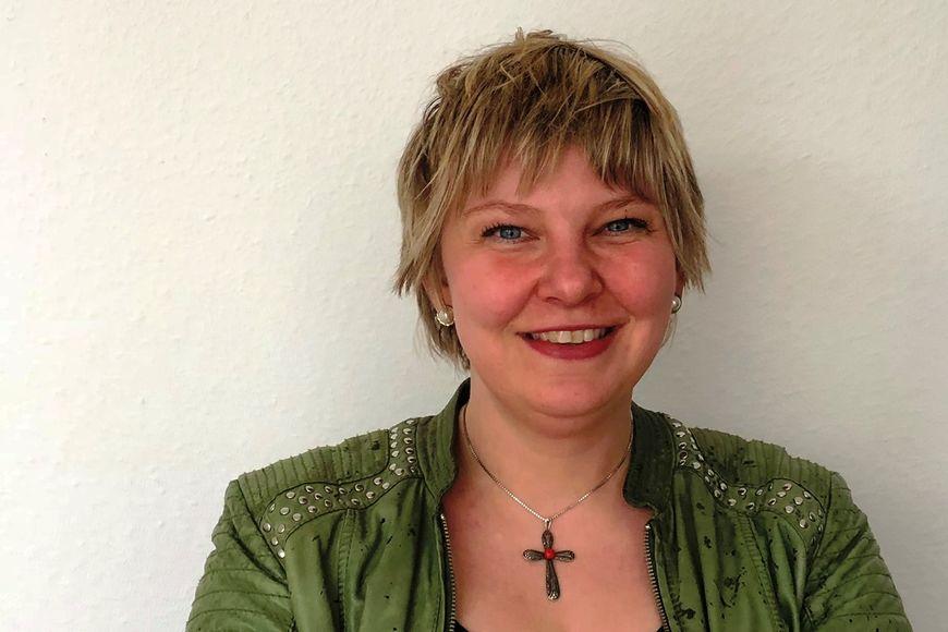 Das Portrait einer Frau mit grüner Jacke. Sie trägt eine Kette mit einem Kreuz. - Copyright: Ines Langhorst