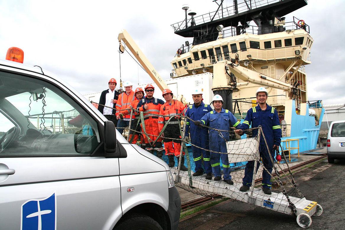 Die Crew eines Schiffes steht auf dem mobilen Landungssteg zwischen Schiff und Festland und schaut in die Kamera. Links im Bild, direkt vor dem Schiff, sieht man das Führerhaus vom Auto der Seemannsmission.
