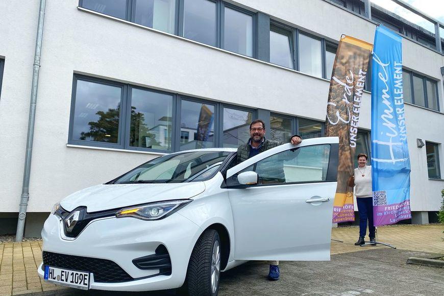 Zwei Personen stehen vor einem weißen E-Auto und lächeln in die Kamera.  - Copyright: Bastian Modrow