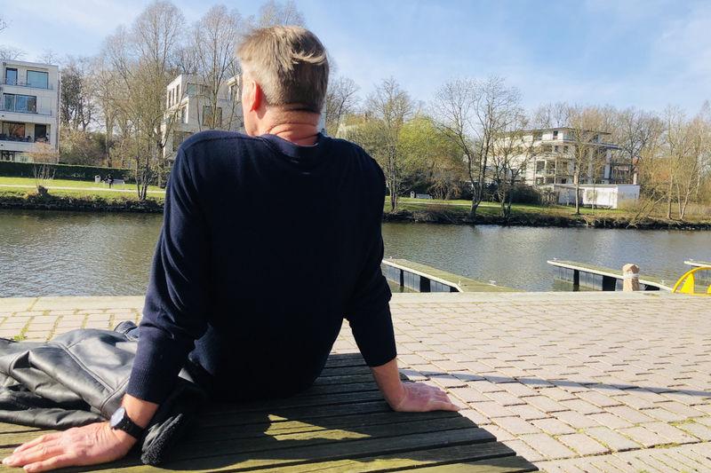 Ein Mann sitzt allein auf einer Bank.