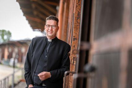 Ein Mann im schwarzen Anzug, mit Brille lehnt an der roten Holzwand einer Remise.  - Copyright: Guido Kollmeyer