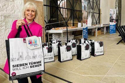 Heike Schumacher hält eine 7-Türme-Tasche hoch, am Griff hängt das neue gestickte Logo. Rechts sieht man weitere Taschen auf dem Boden stehen. - Copyright: Steffi Niemann