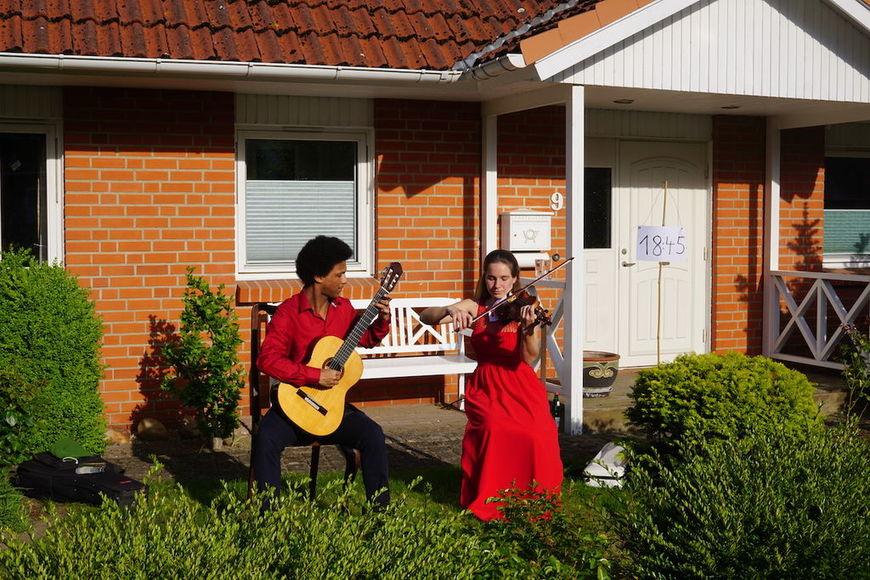 Das Duo Cantolegno spielt in einem  Vorgarten.Julia von Allwörden-Eberlingan der Violine undMatthias Greenslade an der Gitarre. - Copyright: Privat