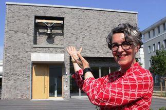 Eine Frau zeigt auf ein Haus. Blauer Himmel, am rechten Bildrand ein Baum. - Copyright: Oliver Pries