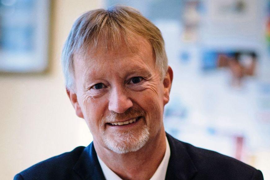 Ein Mann mit Bart, schwarzer Jacke, darunter ein weißer Kragen, schaut freundlich in die Kamera. Im Hintergrund ist unscharf eine Wand mit Bildern erkennbar.