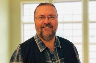 Ein Mann mit Bart und Brille blickt lächelnd in die Kamera. Im Hinterund ein Sprossenfenster. - Copyright: Kirchenkreis Lübeck-Lauenburg
