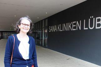Eine Frau mit Brille, weißer Bluse und blauer Jacke steht vor einem Eingangsbereich. Im Hintergrund ist die Aufschrift Sana Kliniken Lübeck zu lesen. - Copyright: Oliver Pries
