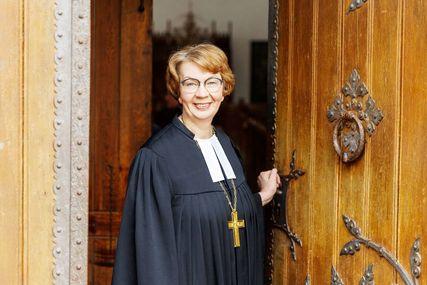 Eine Frau im Talar mit Bischofskreuz kommt aus einer Kirchentür heraus. Sie lächelt freundlich. - Copyright: Nordkirche/Marcello Hernandez