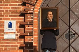 Ein Mensch in schwarzem Parka hält sich ein Porträt von Martin Luther vor das Gesicht. Im Hintergrund eine Kirchentür und ein Schild 'Tritt ein!' - Copyright: Constanze Oldendorf
