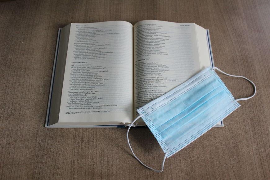Auf einem Holztisch liegt eine aufgeschlagene Bibel. Darauf liegt eine OP-Maske. - Copyright: Georg Gemander