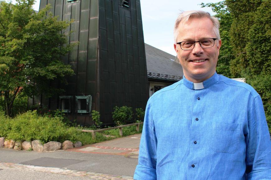 Außenaufnahme: Ein Mann mit blauem Hemd im Halbprofil. Im Hintergrund ein Busch und ein Gebäude. - Copyright: Oliver Pries