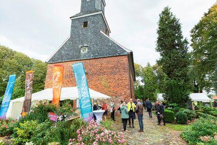 Eine Kirche, Menschen vor der Kirche, Fahnen und ein Pagodenzelt. - Copyright: Dirk Eisermann