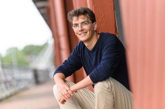 Ein Mann mit Brille sitzt auf dem Rand eines Absatzes und blickt freundlich in die Kamera. - Copyright: Gudio Kollmeier