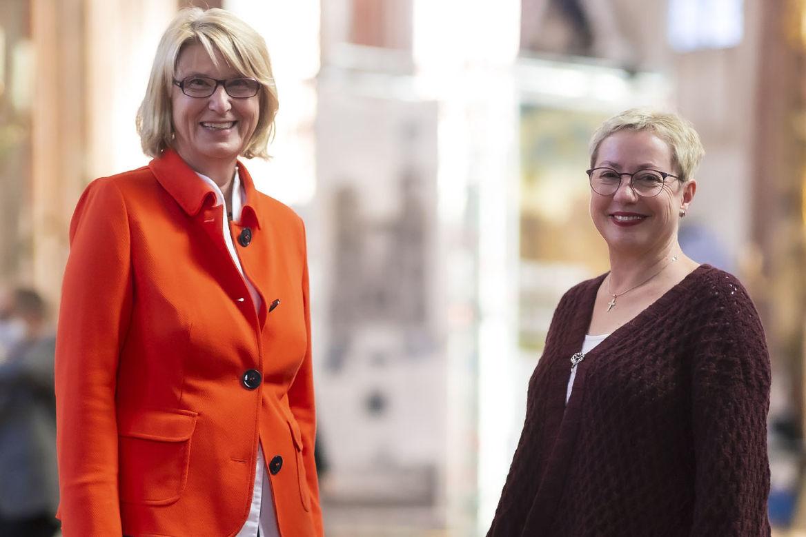 Auf der Linken Seite steht Frauke Eiben in einer weißen Bluse und einem orangen Jacket, auf der rechten Seite Petra Kallies mit einem braunen Strickoberteil. Beide lächeln in die Kamera.  - Copyright: Agentur 54° | Felix König