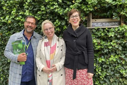 Drei Personen stehen lächelnd vor einer mit Efeu bewachsenen Backsteinmauer. - Copyright: Bastian Modrow