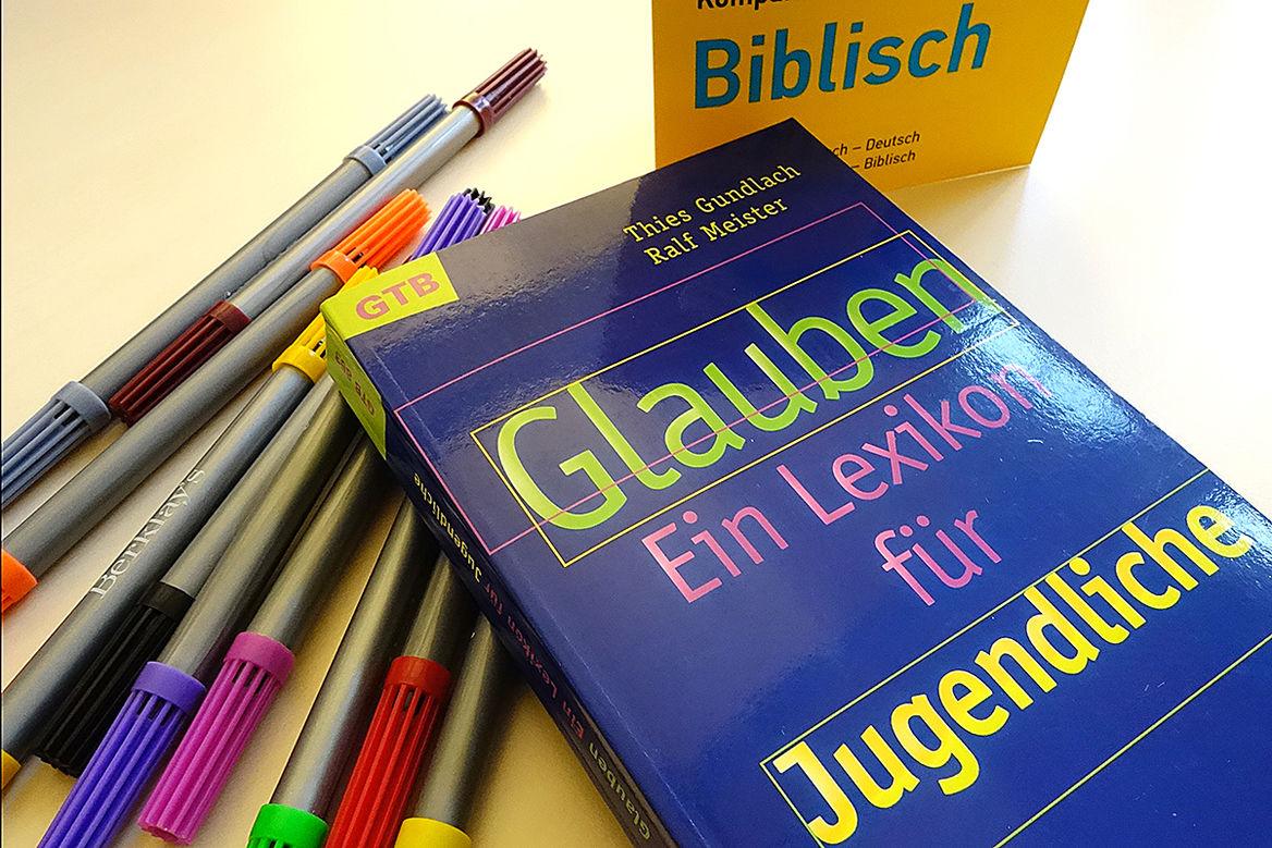 """Buch """"Glauben - Ein Lexikon für Jugendliche"""" liegt auf mehreren bunten Filzstiften"""