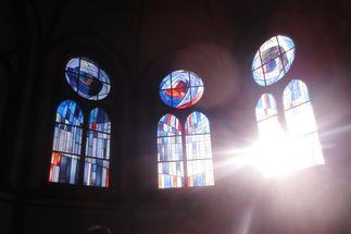 Drei Kirchenfenster. Durch eines scheint die Sonne in den dunklen Kirchenraum. - Copyright: Ines Langhorst