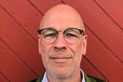 Das Portrait eines Mannes mit Brille. Ein roter Hintergrund - Copyright: Marion Barsuhn (privat)