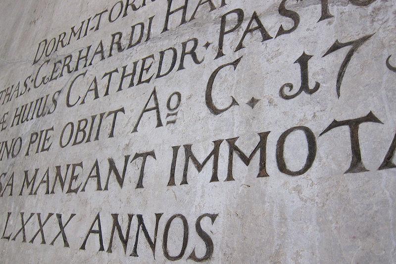 Auf dem Foto ist die inschrift in einer Kirchenwand zu sehen.