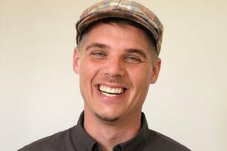 Ein junger Mann mit modischer karierter Mütze lacht herzlich in die Kamera - Copyright: Holger Wöltjen