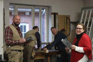 In einer Werkstatt schauen zwei Menschen freundlich in die Kamera. Der Mann links trägt traditionelle Maurerkleidung und die Frau rechts einen roten Poncho. Beide halten ein hellblaues Buch in der Hand. Im Hintergrund arbeiten zwei Männer an einem Balken. - Copyright: Georg Gemander