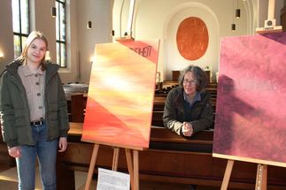 Zwei Frauen stehen zwischen zwei Staffeleien, darauf stehen großformatige Bilder. Im Hintergrund ist der Altarraum der Lutherkirche Lübeck erkennbar. - Copyright: Oliver Pries