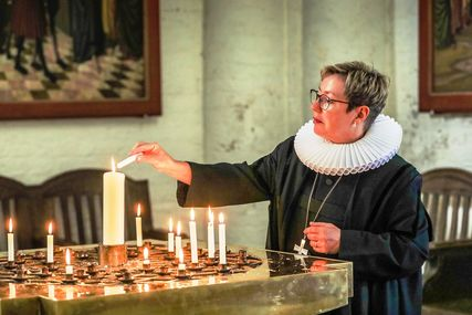 Eine Frau im Talar, Kerzen, im Hintergrund ein Kirchraum. - Copyright: Kirchenkreis Lübeck-Lauenburg