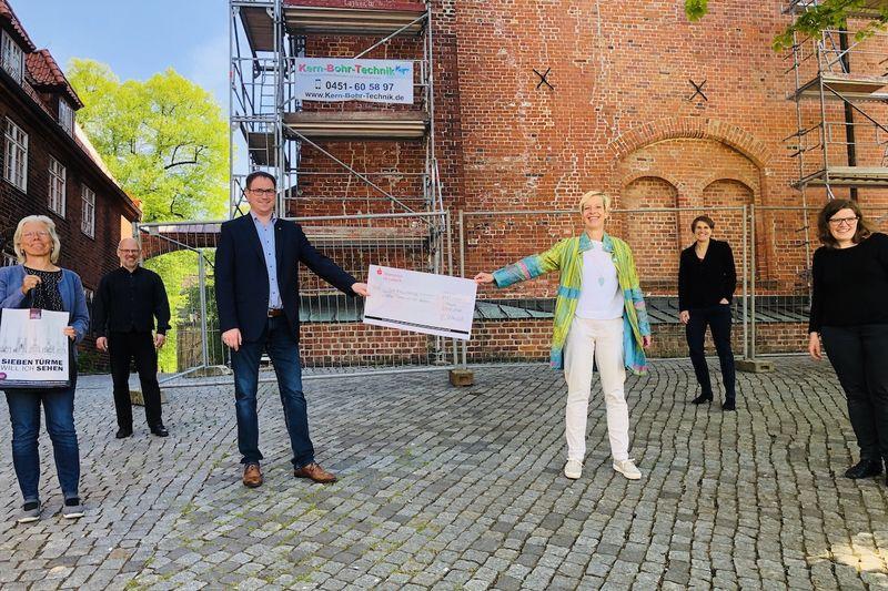 Renate Somrau vom Verein Lübecker Stadtführer e.V., Pastor Martin Klatt, Bürgermeister Jan Lindenau, Petra Ulrich, Pastorin Margrit Wegner und Vikarin Carolin Sauer bei der Scheck-Übergabe am Dom zu Lübeck.