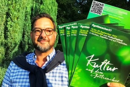 Ein Mann mit Brille hält Flyer in die Kamera. Sie sind grün.  - Copyright: Kirchenkreis Lübeck-Lauenburg