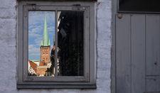 Durch ein Fenster sieht man den St.-Petri-Turm