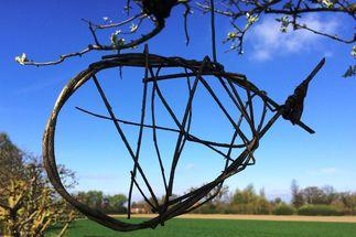 Die Umrisse eines Fisches aus Weidenruten. Sie hängen in einem Baum, im Hintergund Landschaft & Himmel. - Copyright: Ines Langhorst