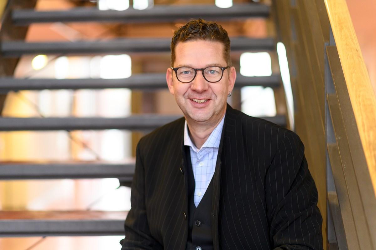 Ein Mann mit kurzen, dunklen Haaren und Brille im Portrait. Im Hintergrund eine Treppe.