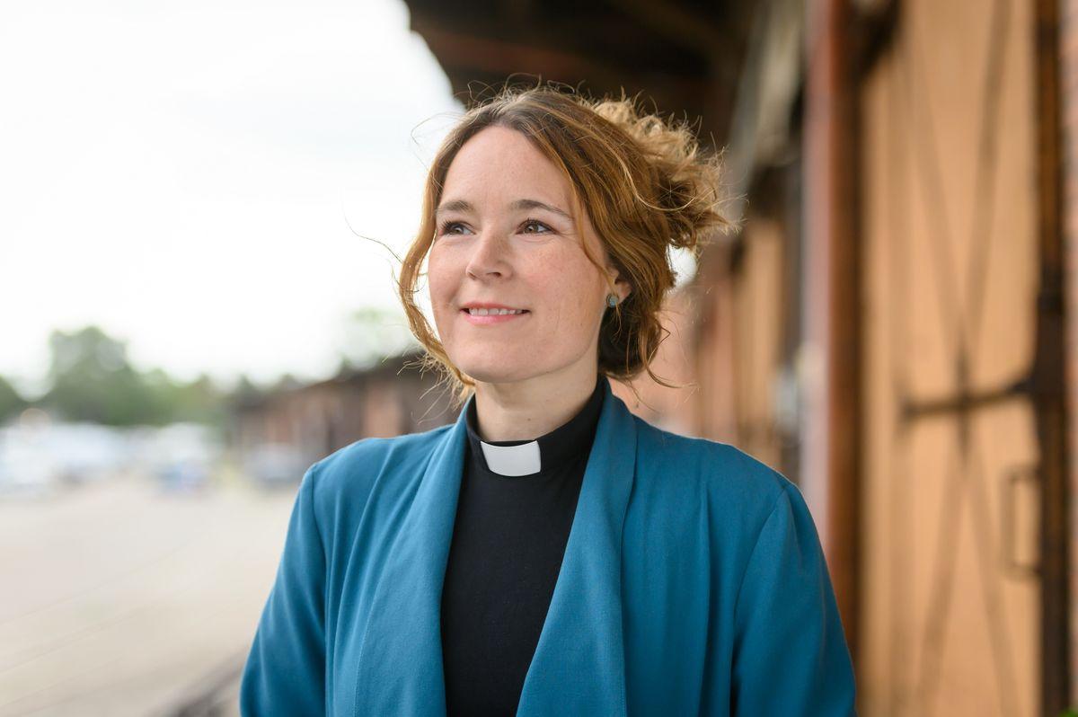 Eine Pastorin mit blauer Jacke und hochgestecktem braunen Haar am Hafenschuppen von Lübeck