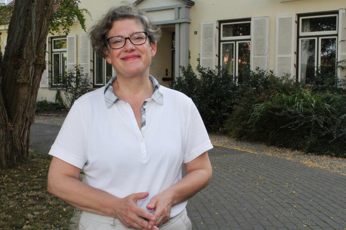 Eine Frau mit Brille. Sie trägt ein weißes Polo-Shirt. Im Hintergrund ein Haus.