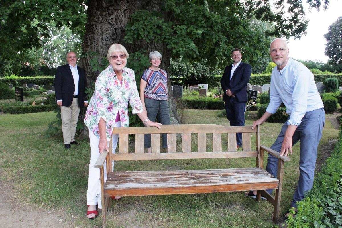 Funf Männer und Frauen auf Abstand rund um eine Holzbank. Im Hintergrund ein Baum.