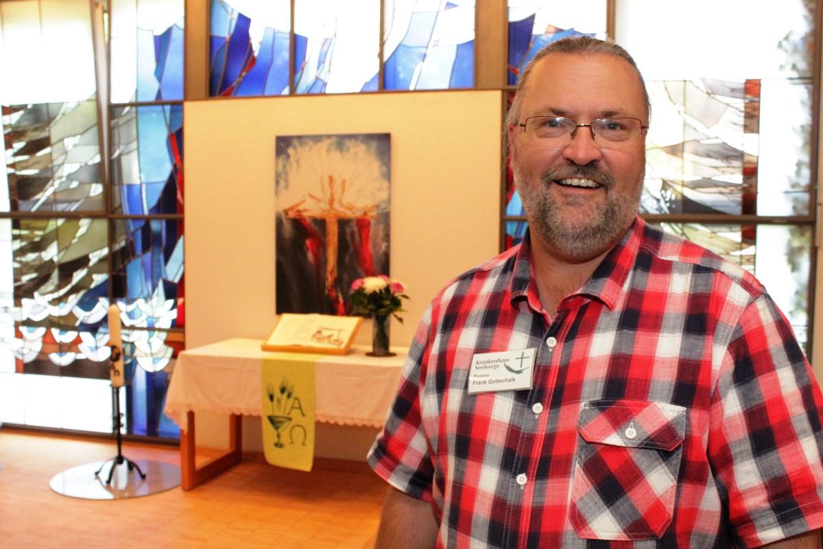 Ein Mann mit Brille. Er trägt ein kariertes Oberhemd. Im Hintergrund ein Altar und bunte Fenster.