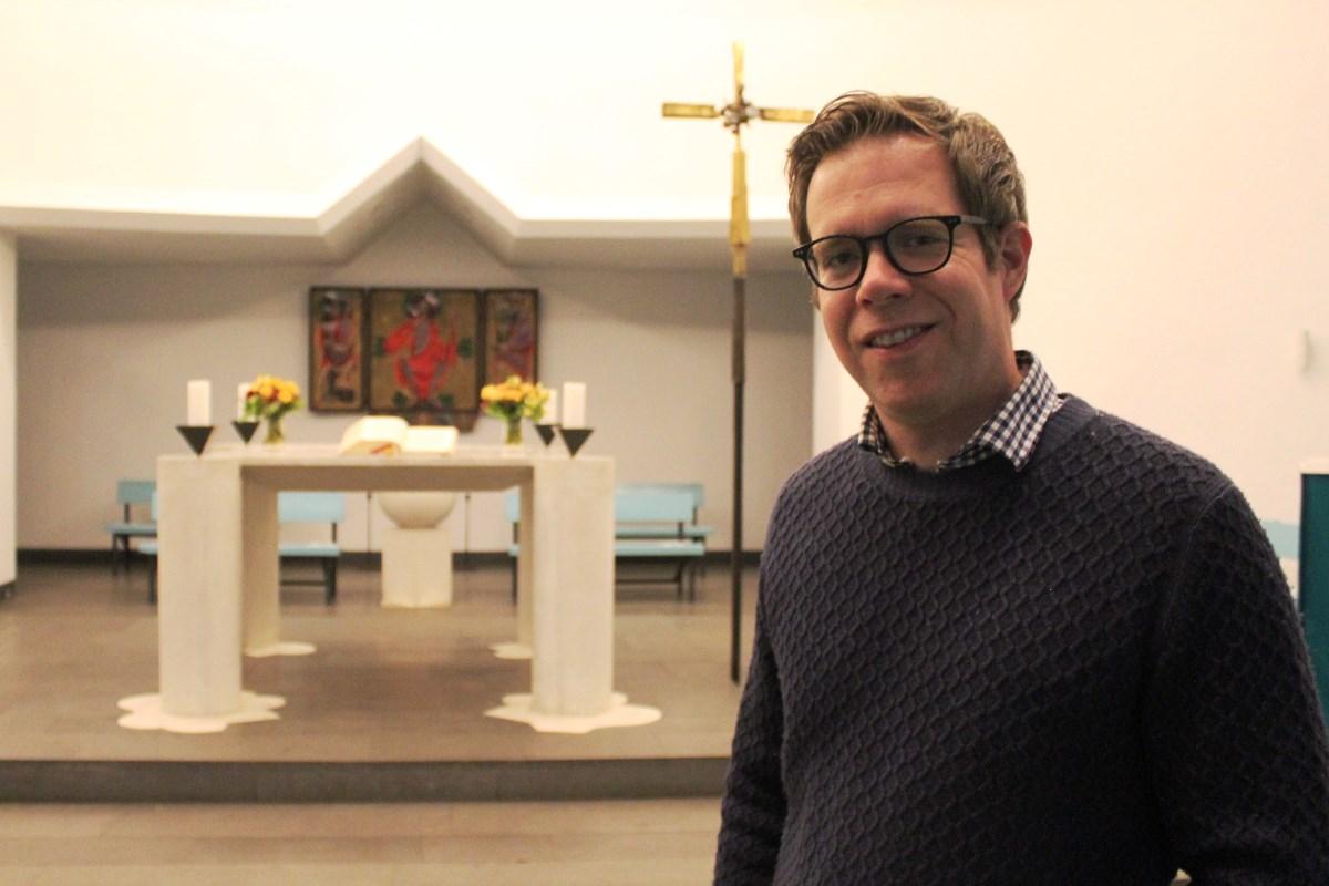 Ein Mann mit Brille, im Hintergrund eine Altar und ein Kreuz.