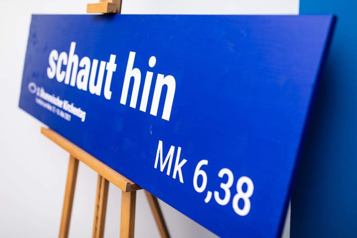 Ein blaues Schild auf einer Staffelei mit der weißen Aufschrift Schaut hin.