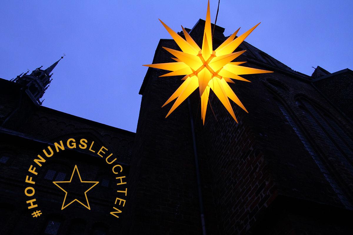 Ein Herrnhuter Stern in der Abenddämmerung vor einer Kirche, das Logo der Aktion ist unten links.