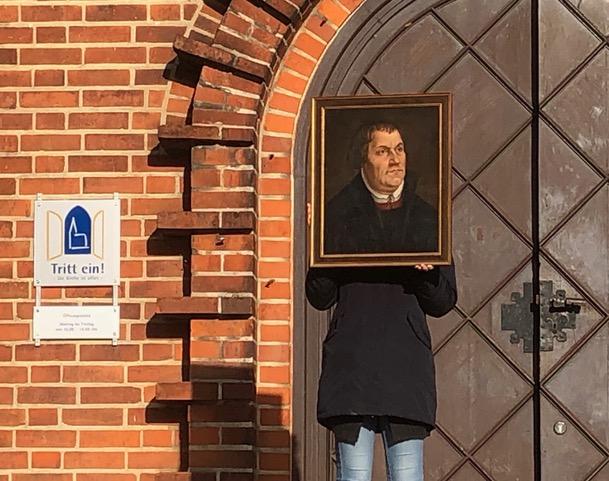 """Ein Mensch in schwarzem Parka hält sich ein Porträt von Martin Luther vor das Gesicht. Im Hintergrund eine Kirchentür und ein Schild """"Tritt ein!"""""""