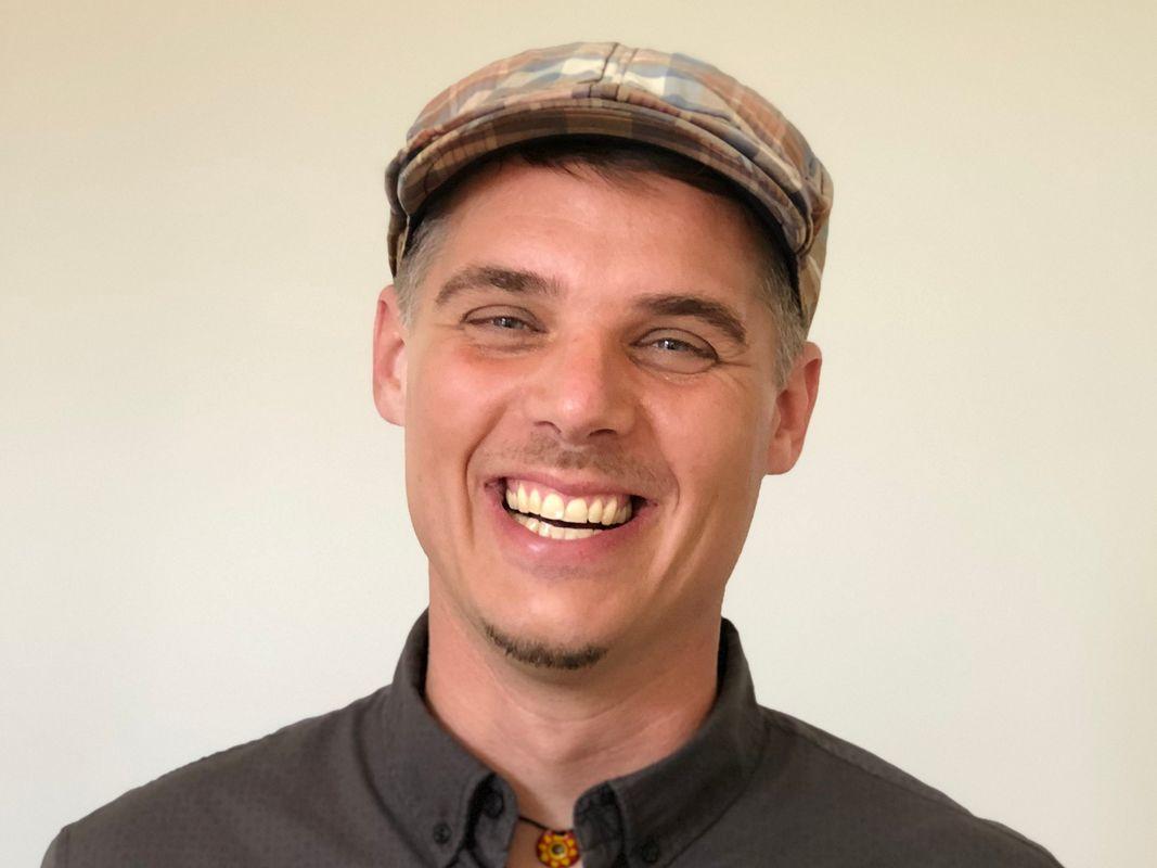 Ein junger Mann mit modischer karierter Mütze lacht herzlich in die Kamera
