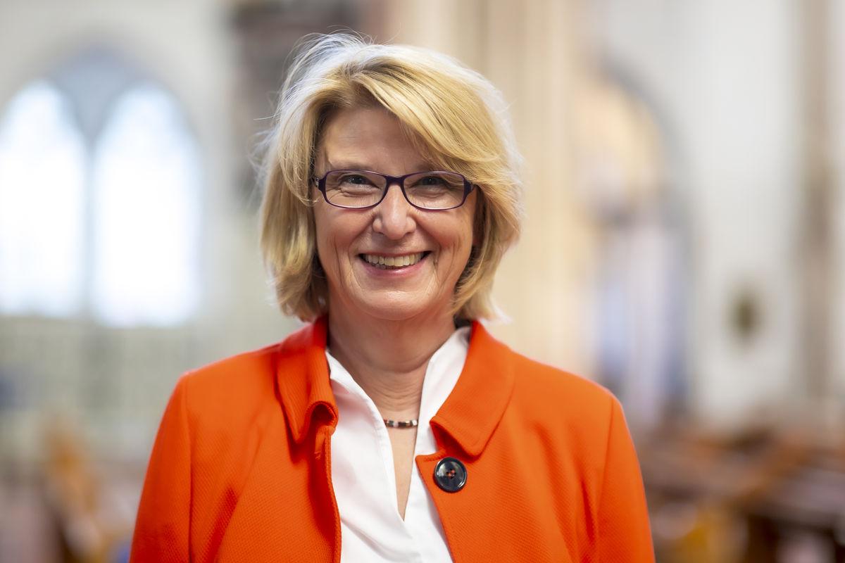 Eine blonde Frau mit Brille und orangefarbener Jacke lächelt freundlich in die Kamera