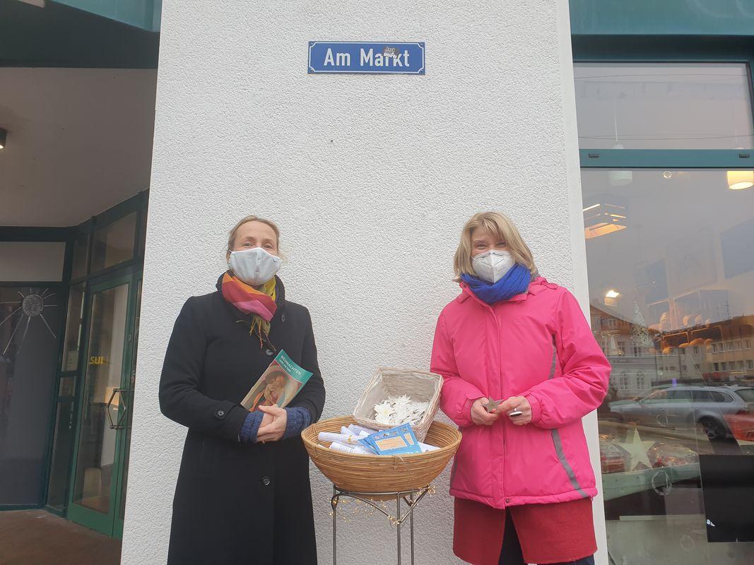 """Zwei Frauen stehen vor einer grauen Wand. Zwischen ihnen steht ein kleiner Korb auf einem Ständer, in dem gerollte Papiere und blaue Flyer liegen. Über ihnen steht auf einem Straßenschild: """"Markt"""""""
