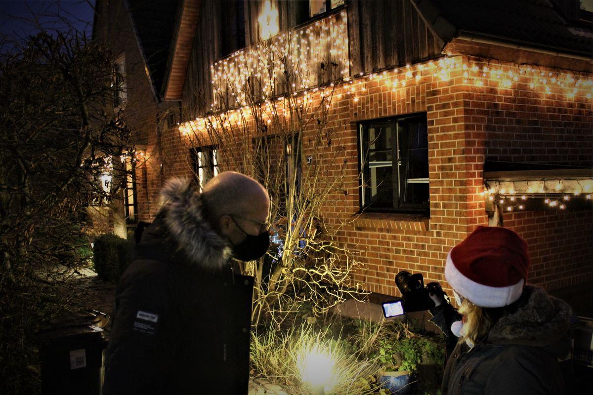 Vor einem weihnachtlich geschmückten Haus stehen zwei Menschen und blicken auf das Display einer Kamera